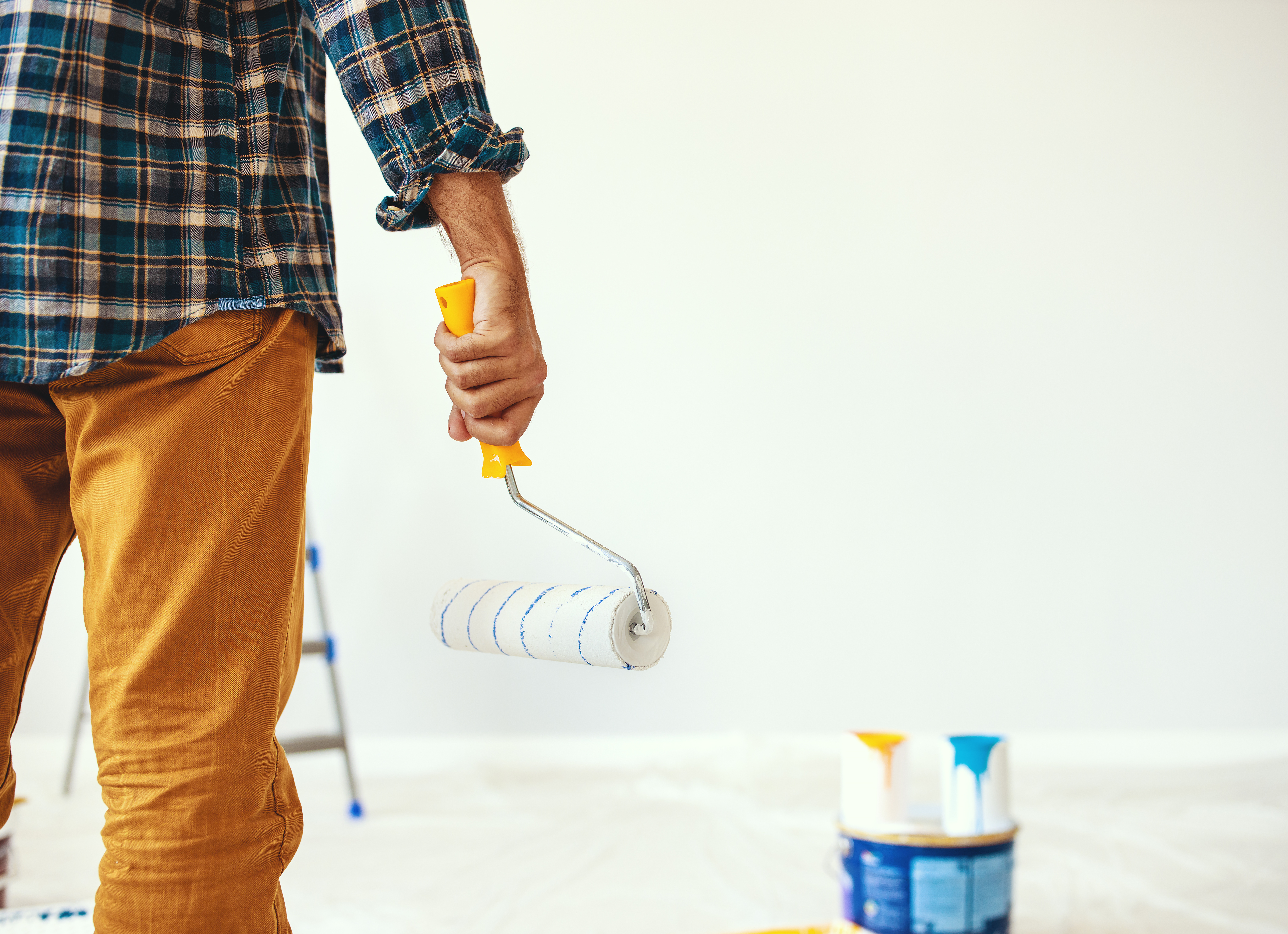 Happy man paints the wall