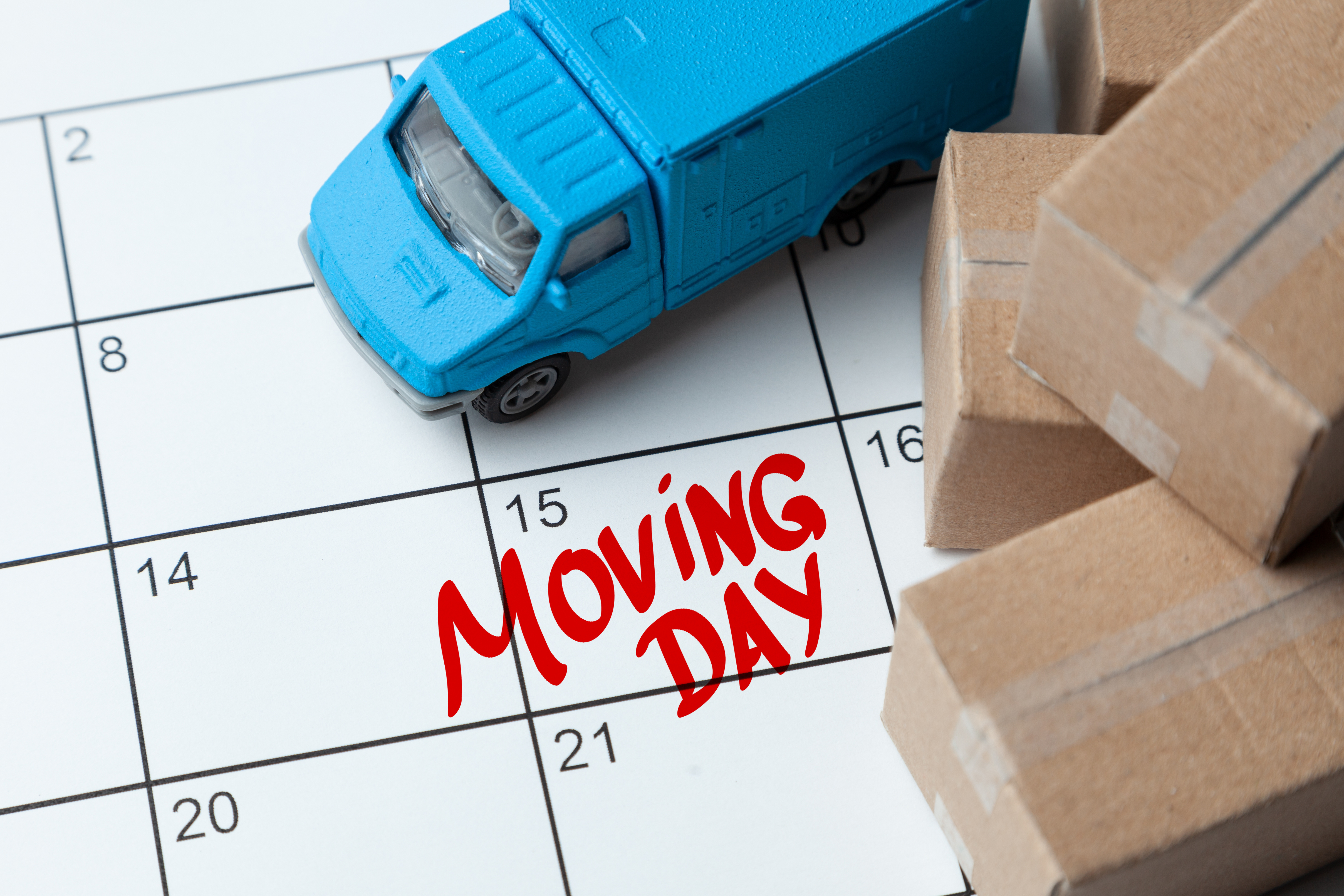 Moving day on the calendar is written in red. Calendar with a note with cardboard boxes and truck