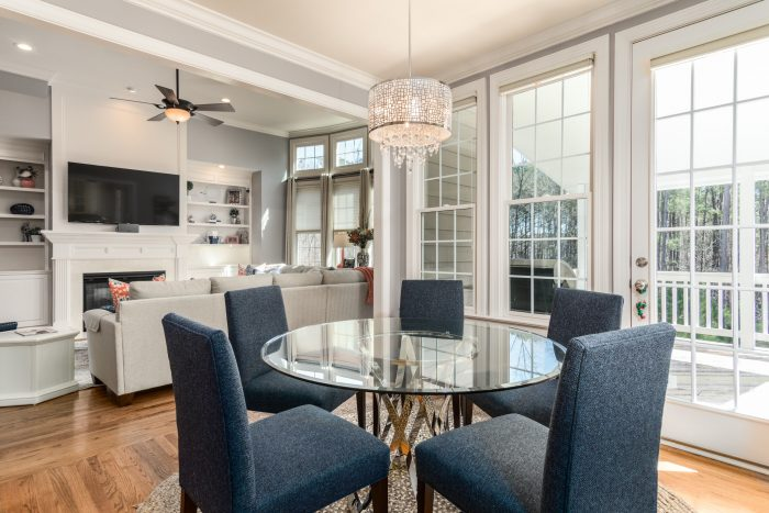 A dining room with blue chairs and a round table
