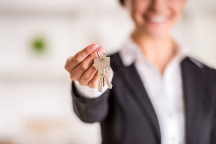 A woman holding out a set of keys