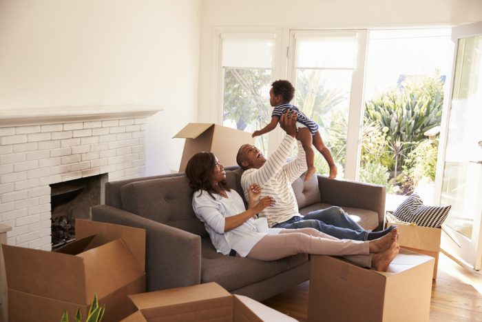 A happy young family sitting on their couch in their empty living room after unboxing