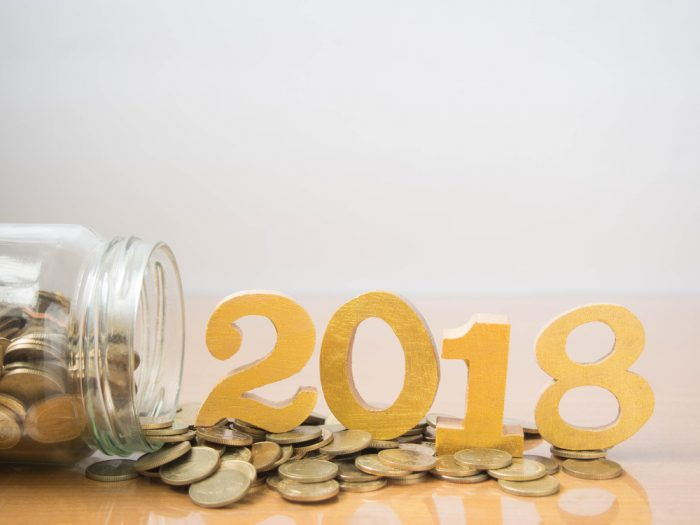 A jar filled with coins spilled over on the table with wooden numbers that say 2018 on top