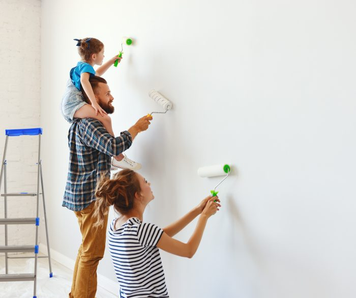 A happy mother, father and child paint a wall